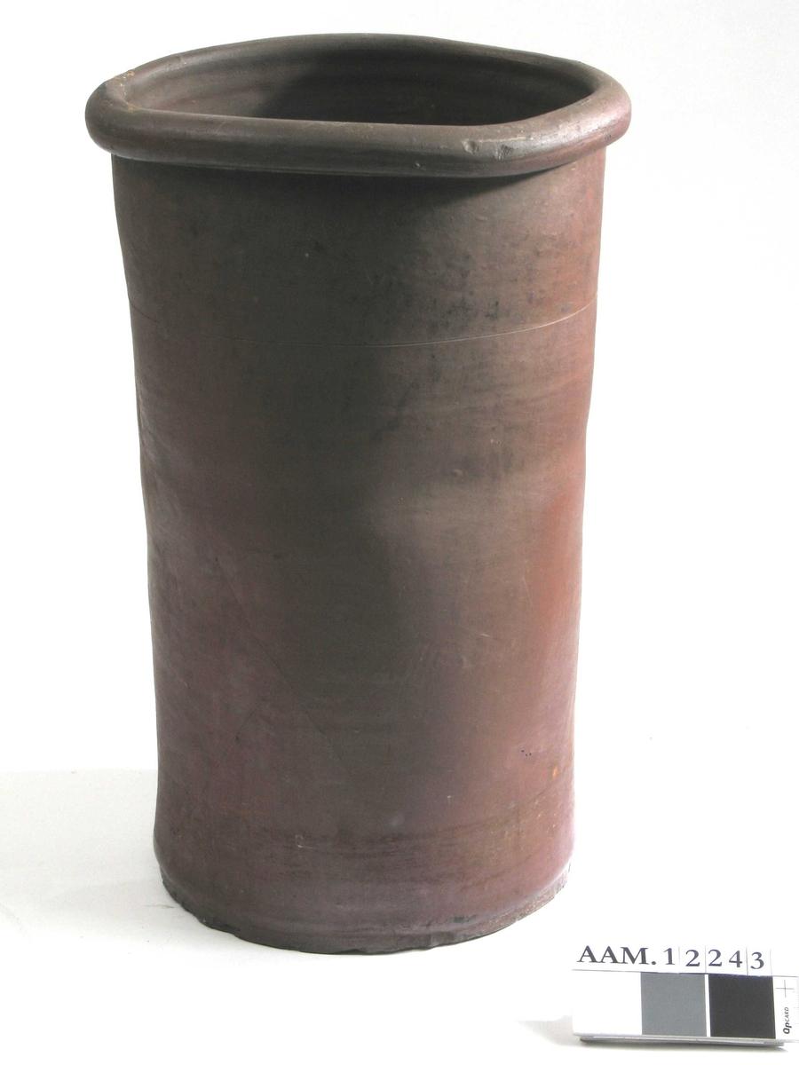 Smørstamp smørbeholder.  Hårdbrent leirtøy,  brunrød/purpurfarget.  Høy rettsidet krukke, øvre halvdel skjevt dreiet, slik at den er ujevnt oval.  Rundet munningsbrem.  Tilstand: god.