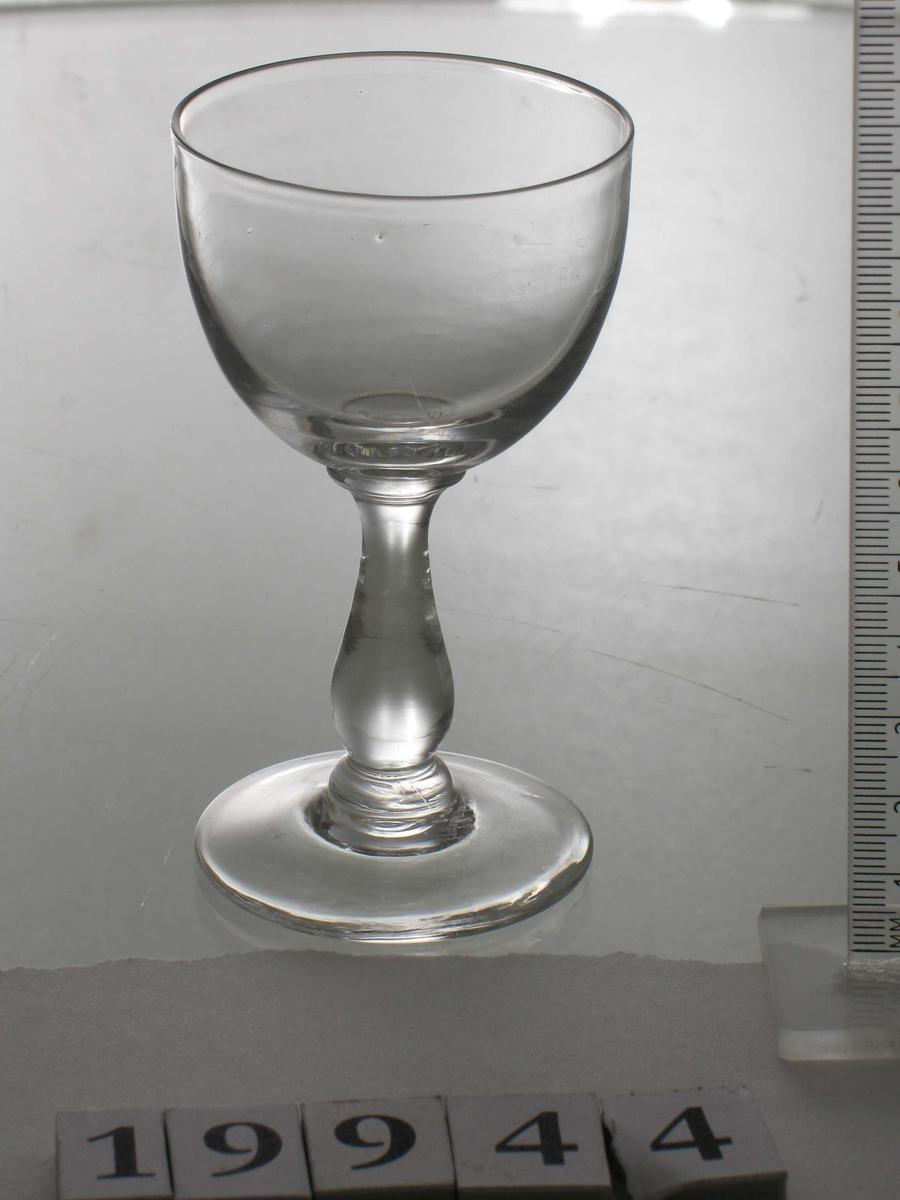 Glass,  klart. Glatt rund fot. vaseformet slank stett, rundbunnet vid klokke  uten dekor eller slipninger.  Tilstand; god.