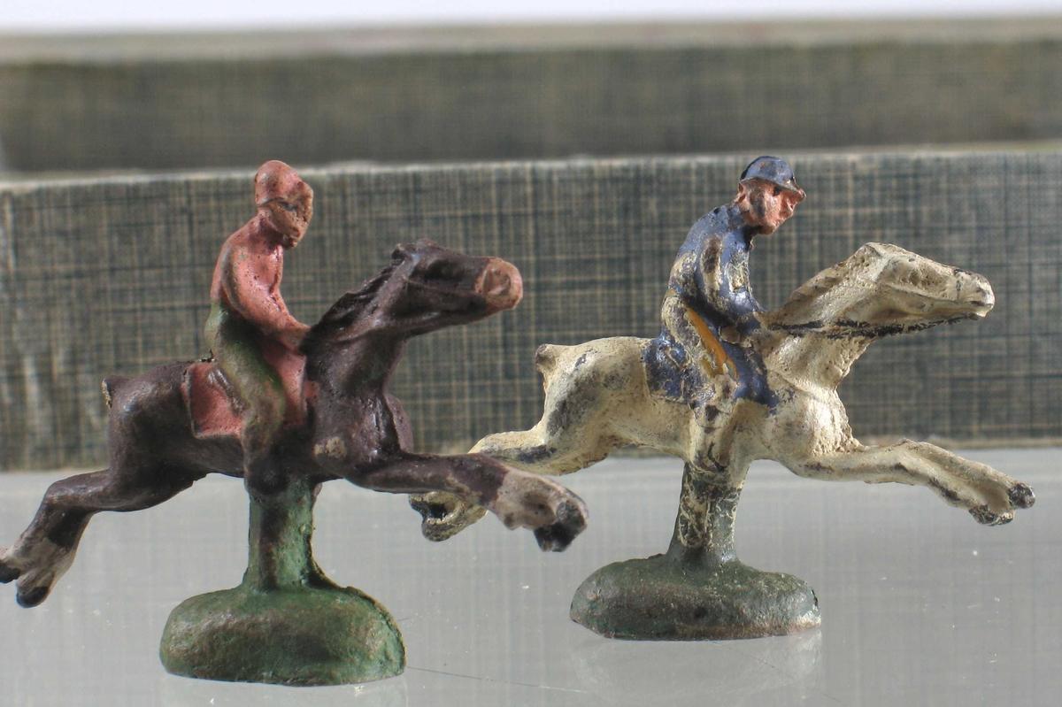 På esken: Hester med ryttere ved hinder, tribuner i bakgrunnen.
