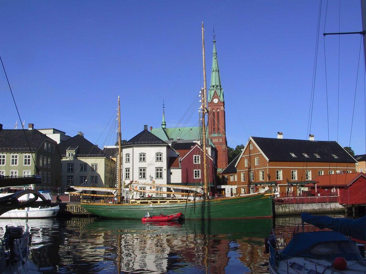 Tyholmen. Kjøpmannsgårdene v Pollen. Kirken i bakgr. Morgenlys.