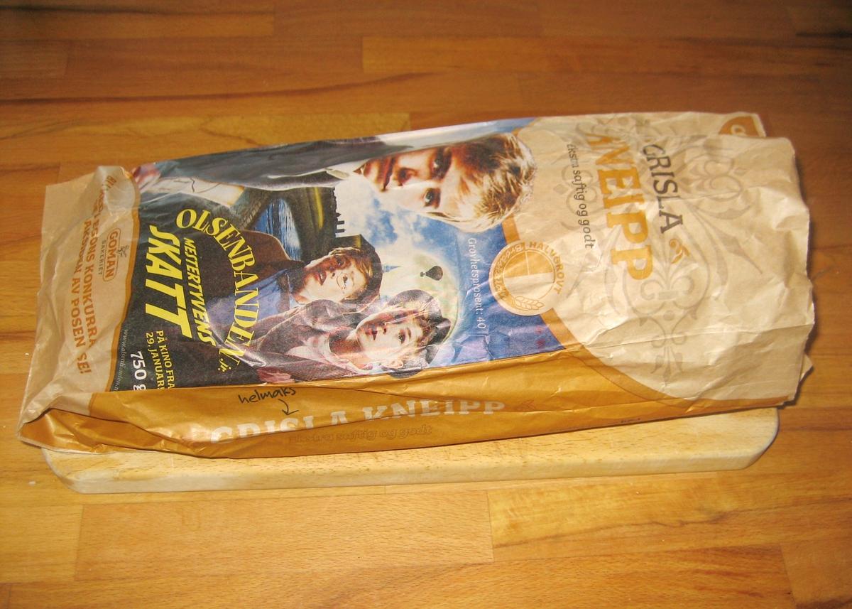 """Motivet på brødposens forside er de tre guttene fra Olsenbanden jr. Egon, Kjell, Benny. Filmens tittel: """"Olsenbanden jr. Mestertyvens skatt"""" står også på forsiden. På baksiden er det en kinobillett."""