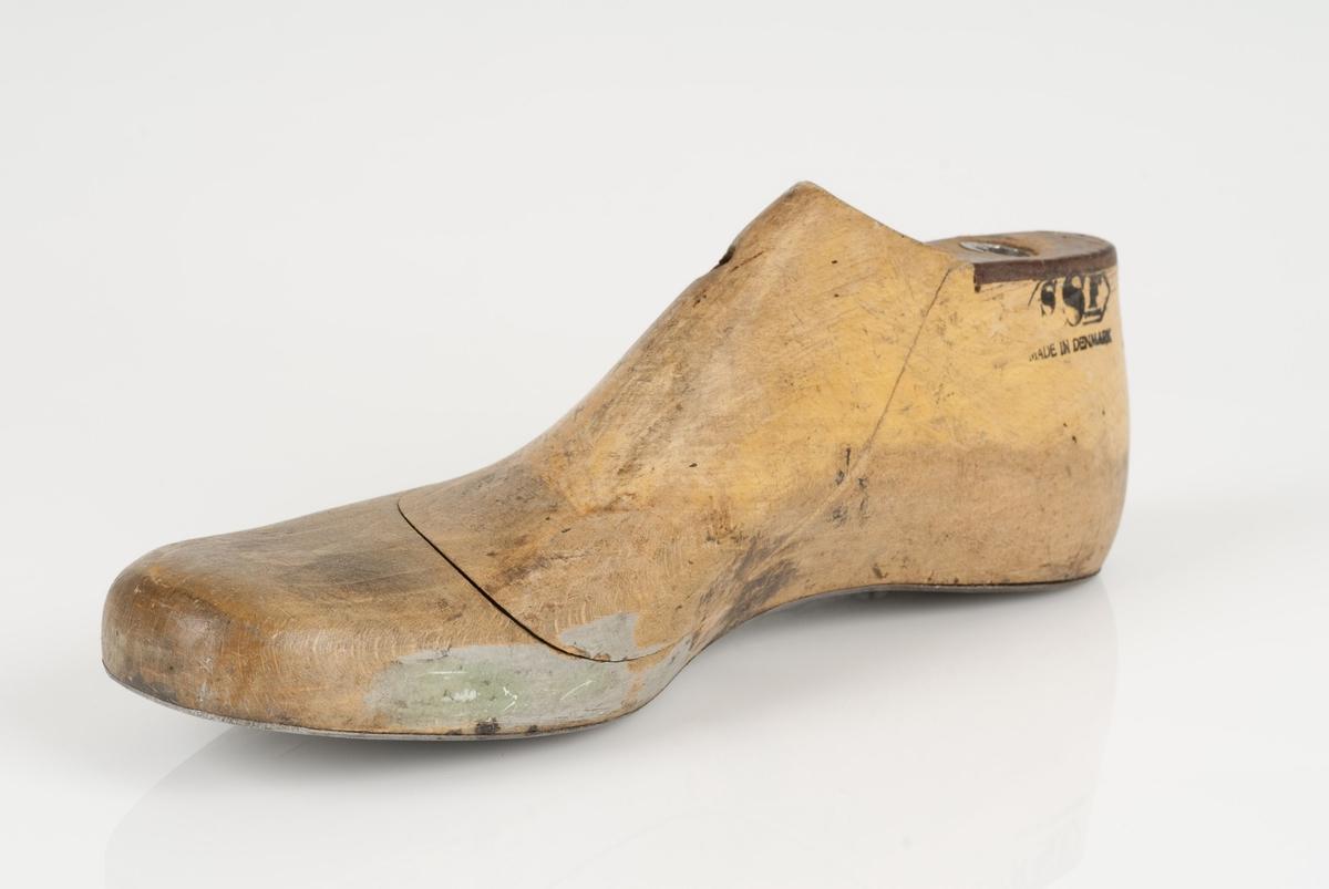 En tremodell i to deler; lest og opplest/overlest (kile). Høyrefot i skostørrelse 40, og 8 cm i vidde. Såle i metall.