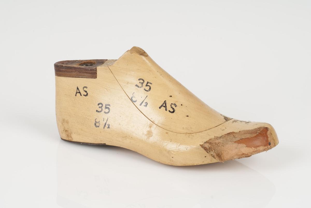 En tremodell i to deler; lest og opplest/overlest (kile). Høyrefot i skostørrelse 35, og 8,5 cm i vidde. Lestekam av skinn. Hælstykke av metall.