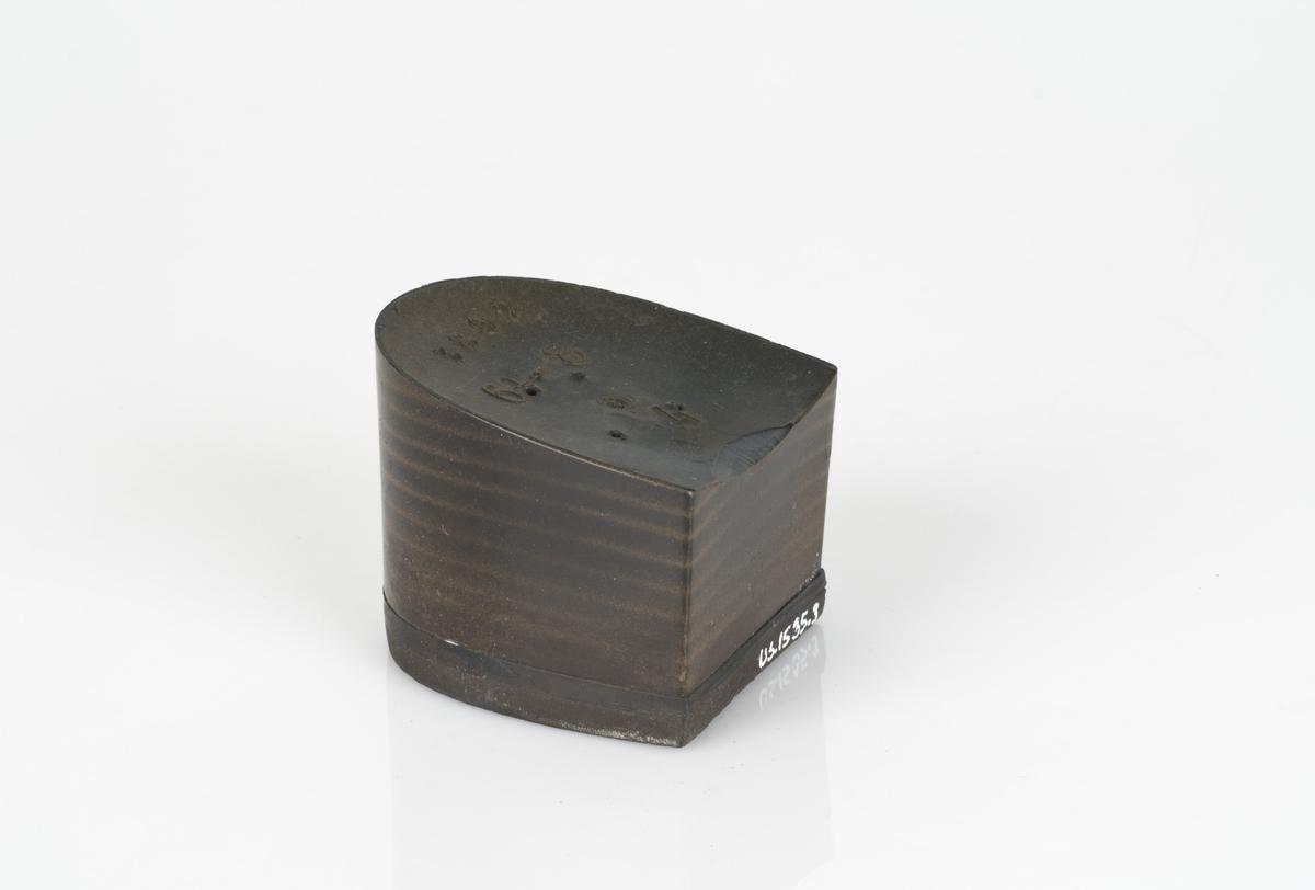 En skohæl av plast i brunfarge. Hælen er moderat (halvhøy) og rett.