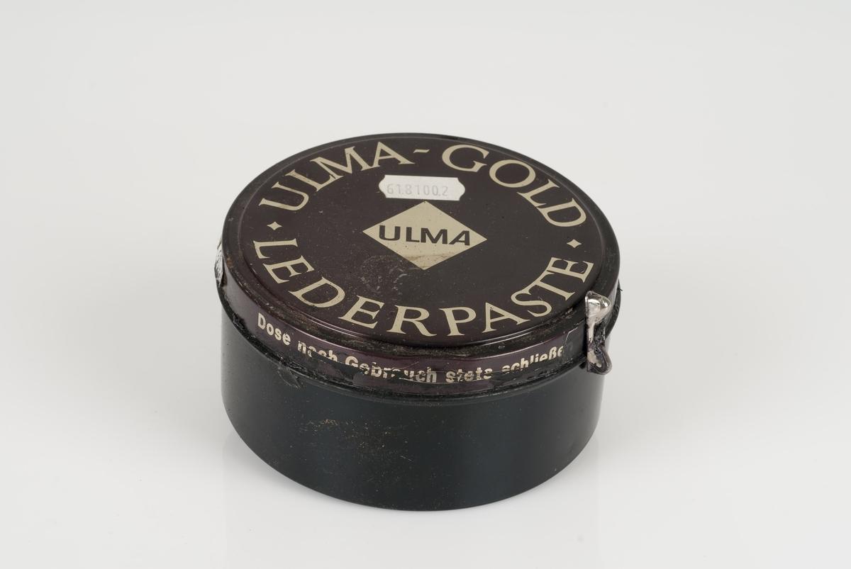 Sort skokrem i rund metallboks Boksen er i fargene brun og sort med påført tekst. Liten hvit påklistret lapp med stempel på boksen.