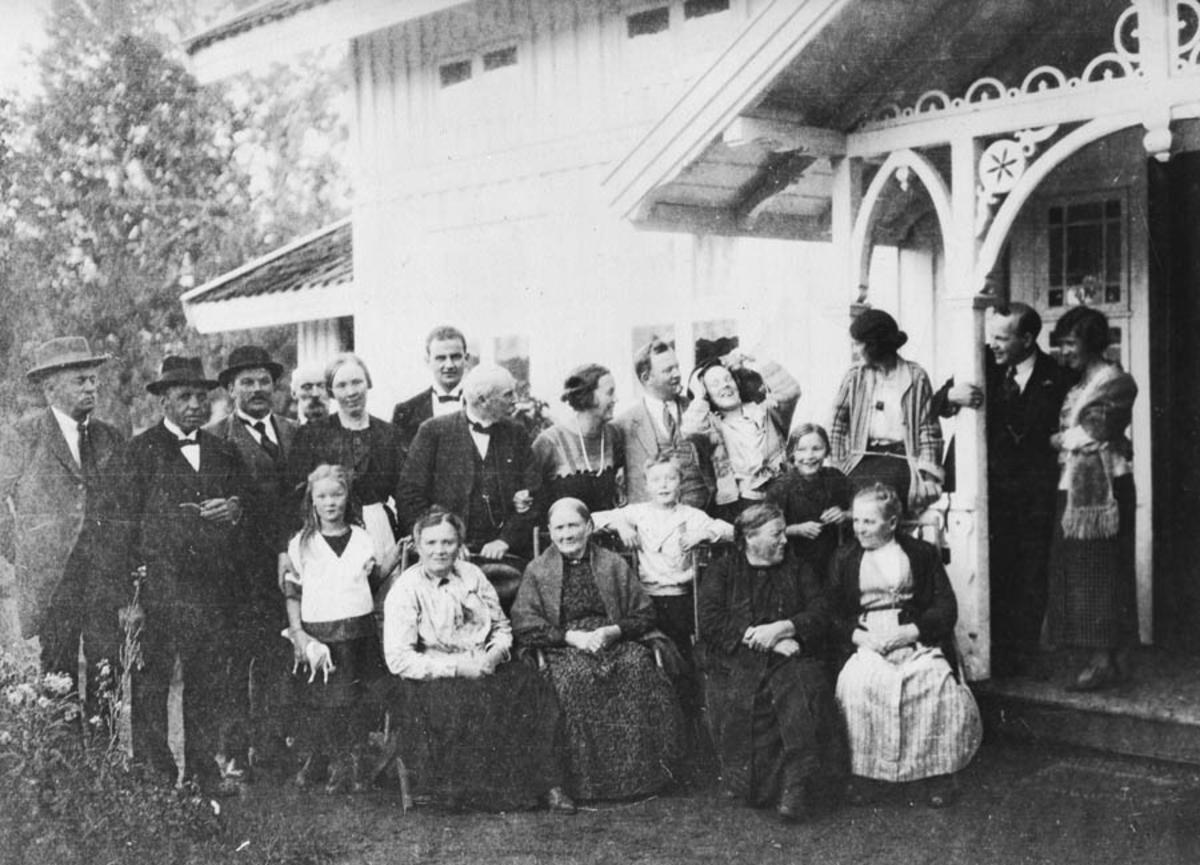 Stor gruppe mennesker utenfor et hus