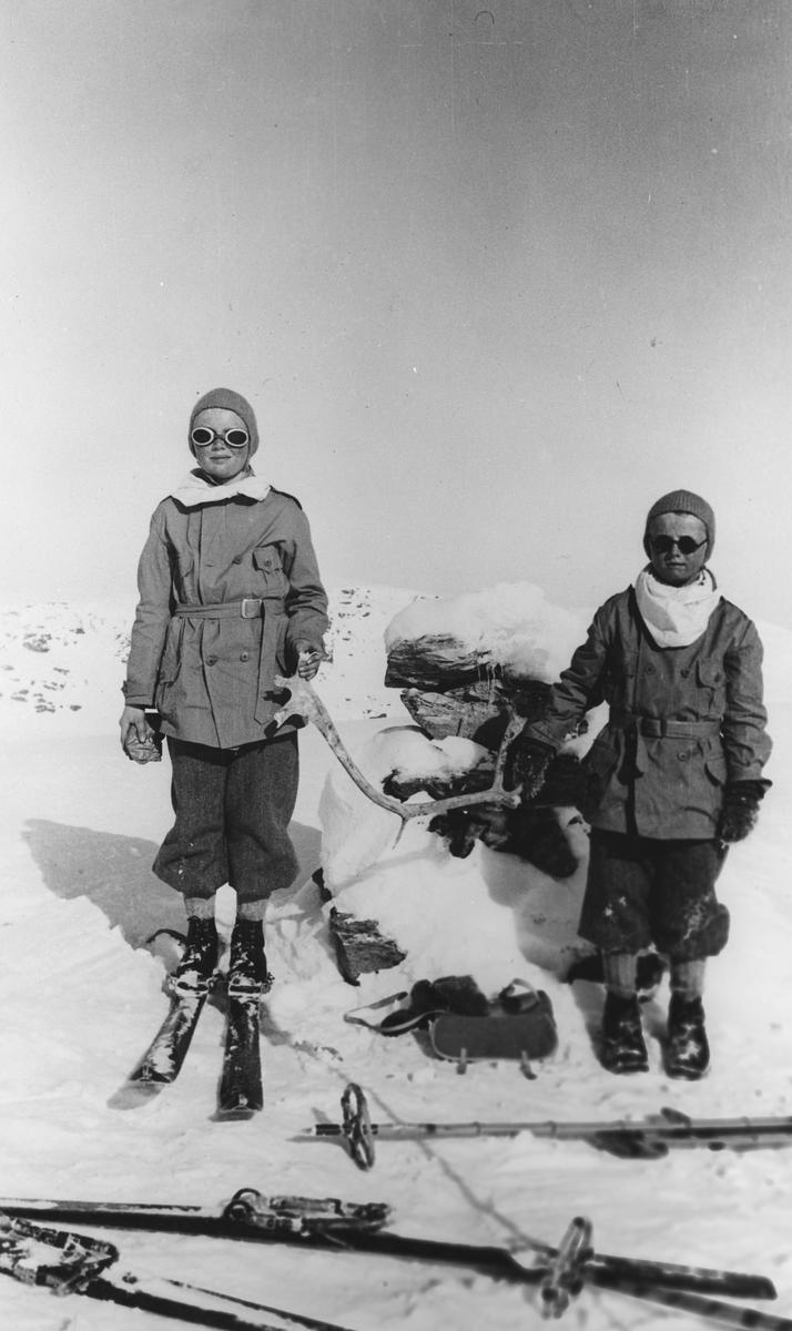 To barn på skitur, på toppen foran varden.