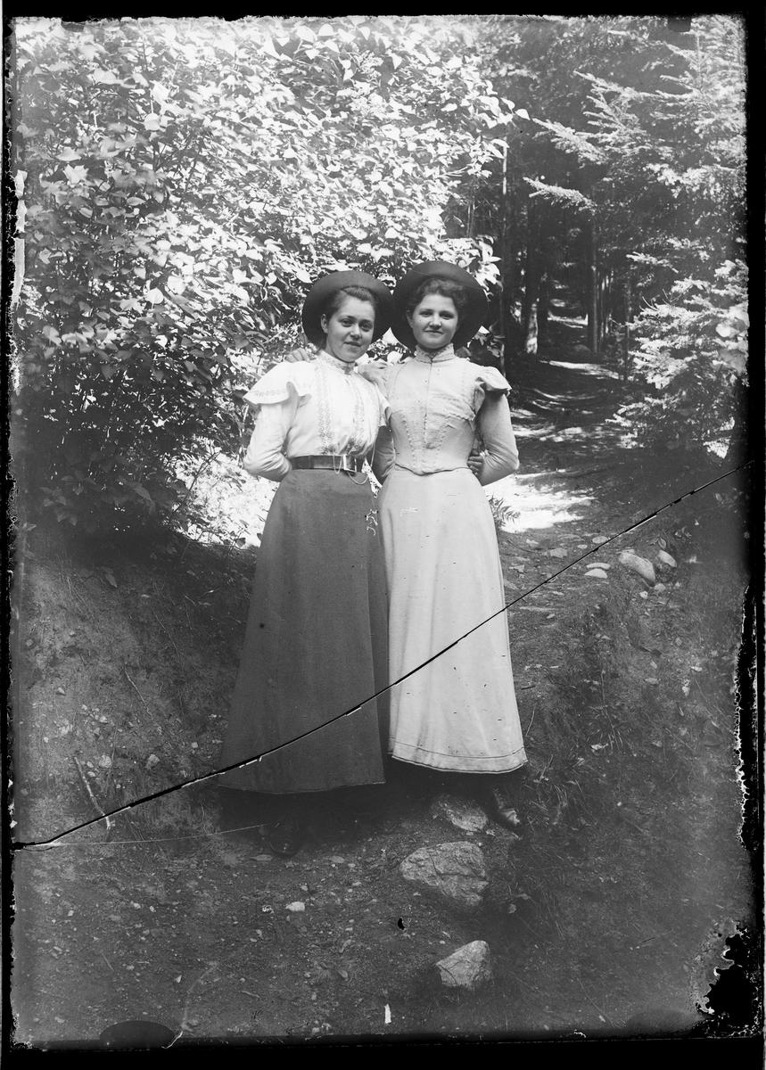 To unge damer under løvverket.