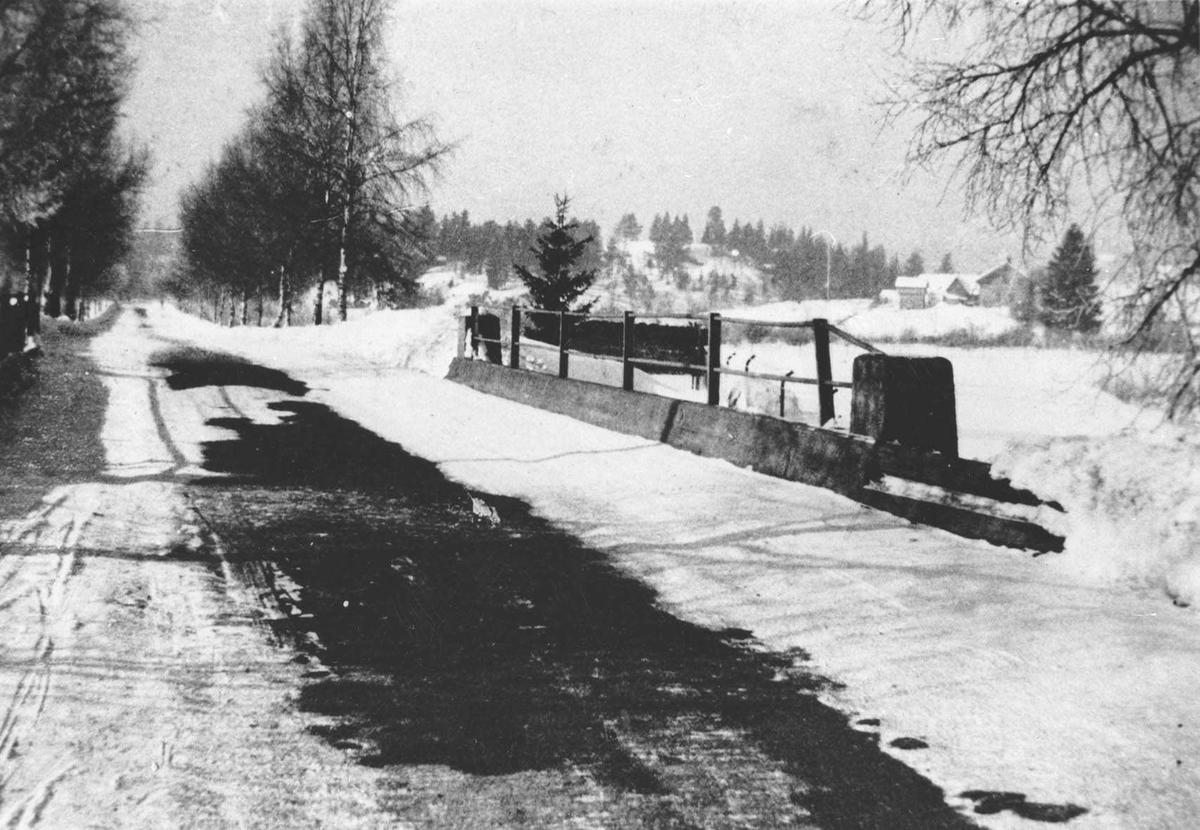 Strømsveien på bro over Losbyelva, fortsetter i en allé. Utsikt mot en gård. Knatten til høyre, retning mot Solheim.