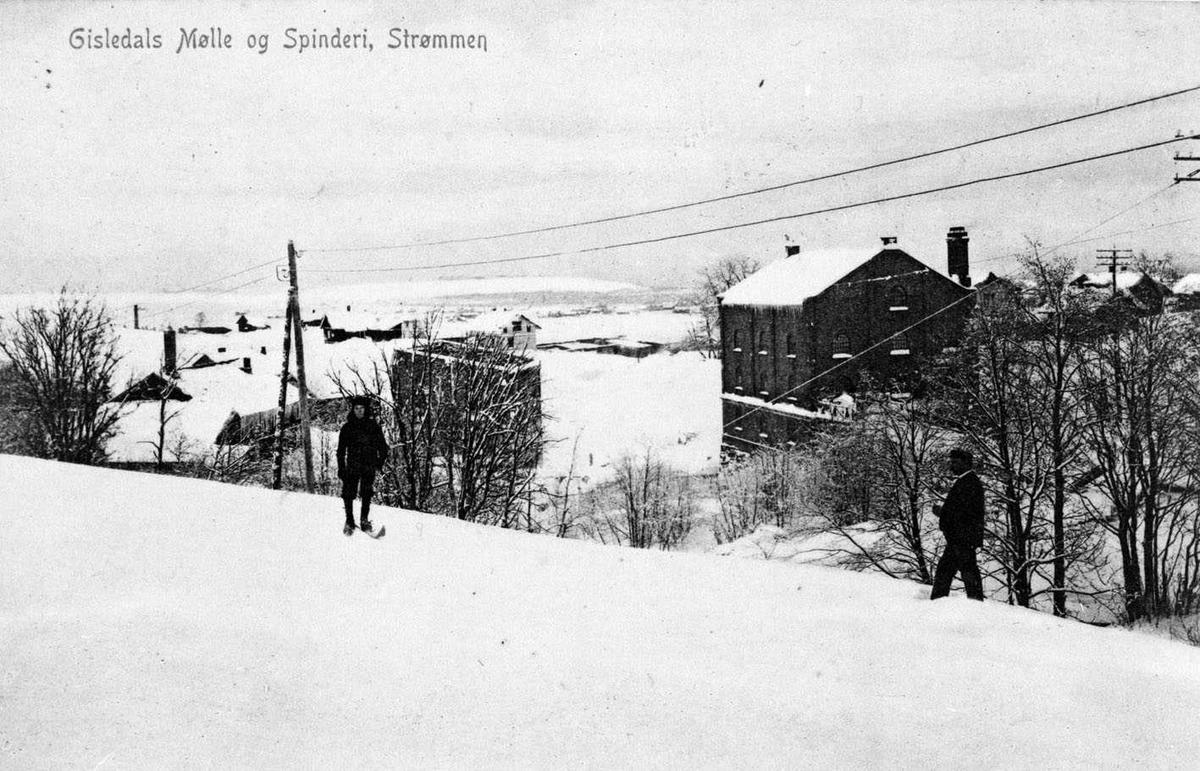 Gisledals Mølle & Spinderi, Strømmen Bildet er tatt fra vest, fra et jorde under Tårnet. To menn, den ene på ski. En murbygning nedenfor mølla ser ut til å mangle tak. (Under bygging?) Postkortfoto: Gisledals Mølle & Spinderi Strømmen