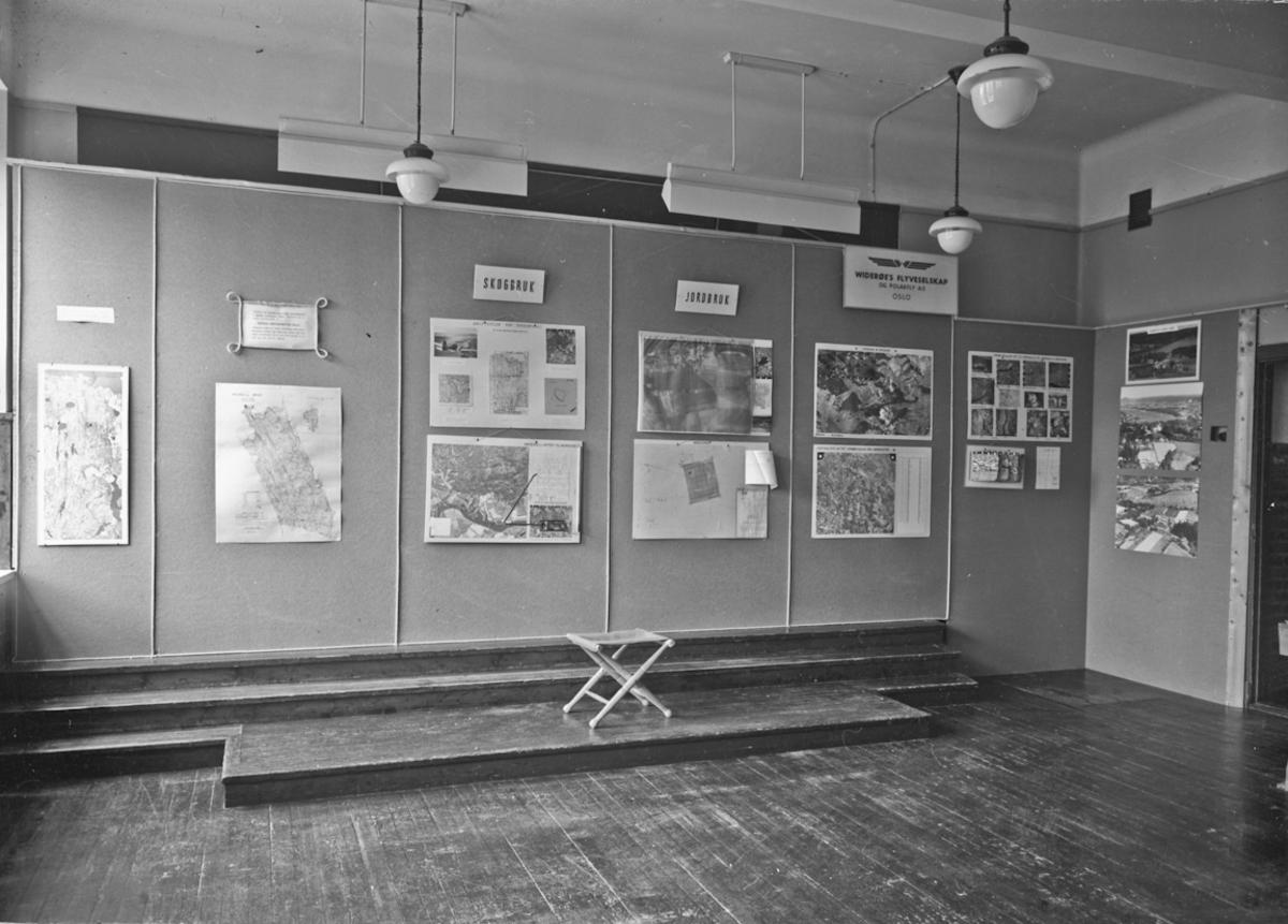Fra bygdeutstillingen i 1955. Om Skogruk, Jordbruk,  Widerøe's Flyveselskap og Polarfly AS OSLO. Utstilling av flyfoto.