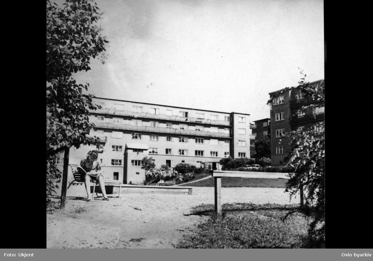 Lekeplass mellom blokker, på folkemunne kalt Leker'n, mellom Båhusveien (som går parallelt med og bak blokken til høyre i bildet) og Bjørn Stallares vei; boligblokkker, lekeplass, kvinne på benk.