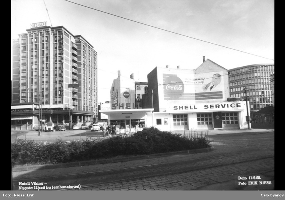 """Shell bensinstasjon i front, Hotell Viking til venstre, åpnet til OL i 1952, """"folkehotell"""", Oslos største hotell fram til 1970-tallet. Arkitekt: Knut Knutsen. Nygata 12 bak til høyre (Traktorhuset), veggreklame. Bilde datert 11. september 1960."""