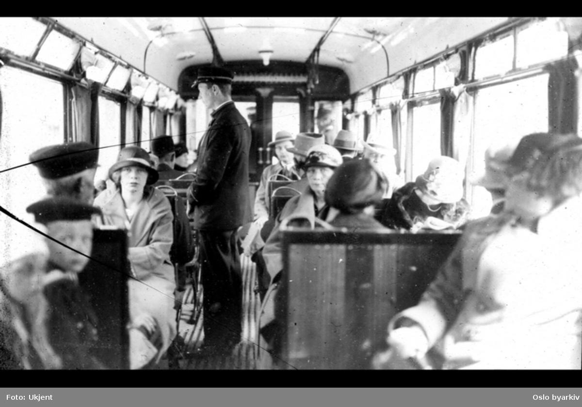 Konduktør og passasjerer i vogn. Mulig feil i tittel, kan være Østensjøbanen.