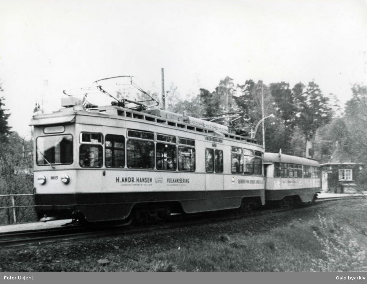 Trikk 1015 (i drift fra 1933 til 1974) med Skabo-tilhenger (kalt Olympiavogn) på Ekebergbanen. Ljabru endeholdeplass. Trikkereklame for H. Andr. Hansen verksted.