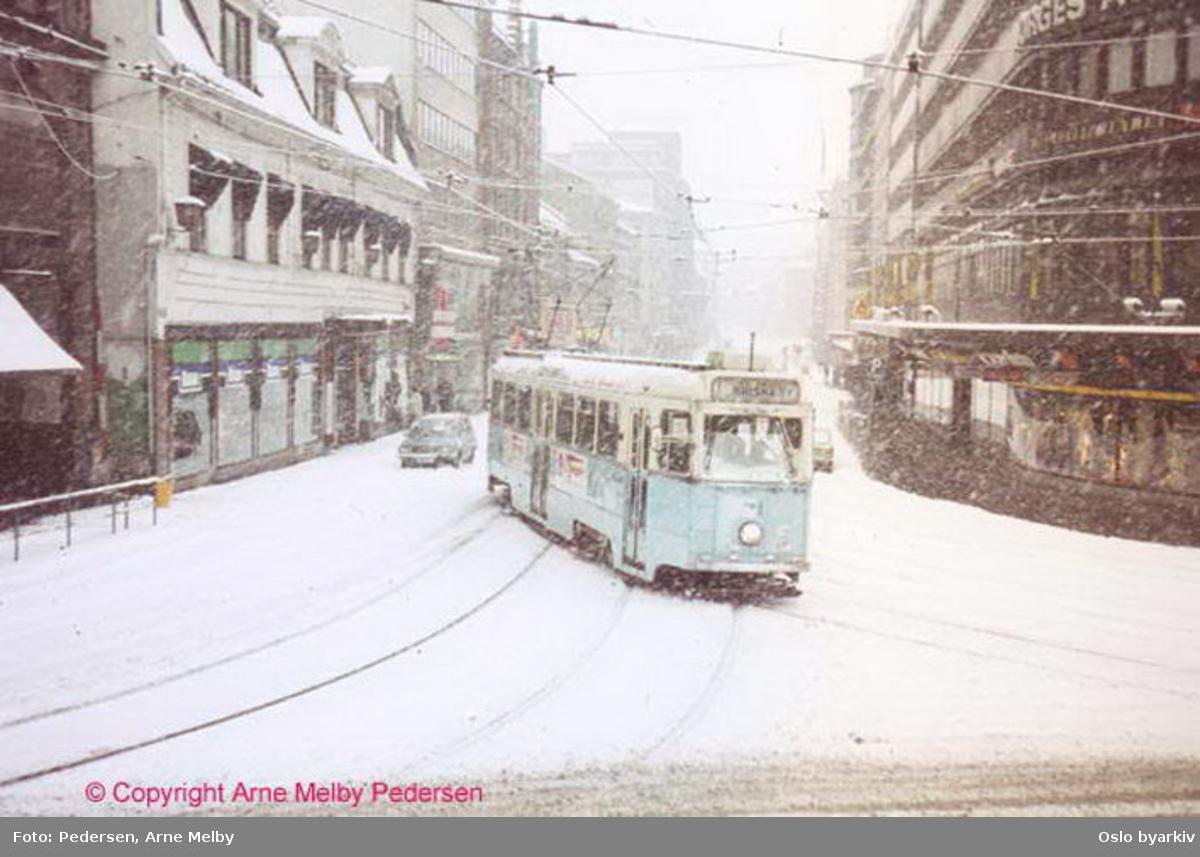 Oslo Sporveier. Trikk motorvogn 221 type Høka MBO linje 1 svinger inn i Dronningens gate fra Storgata, ved Kirkeristen. Vinterbilde, snøvær.