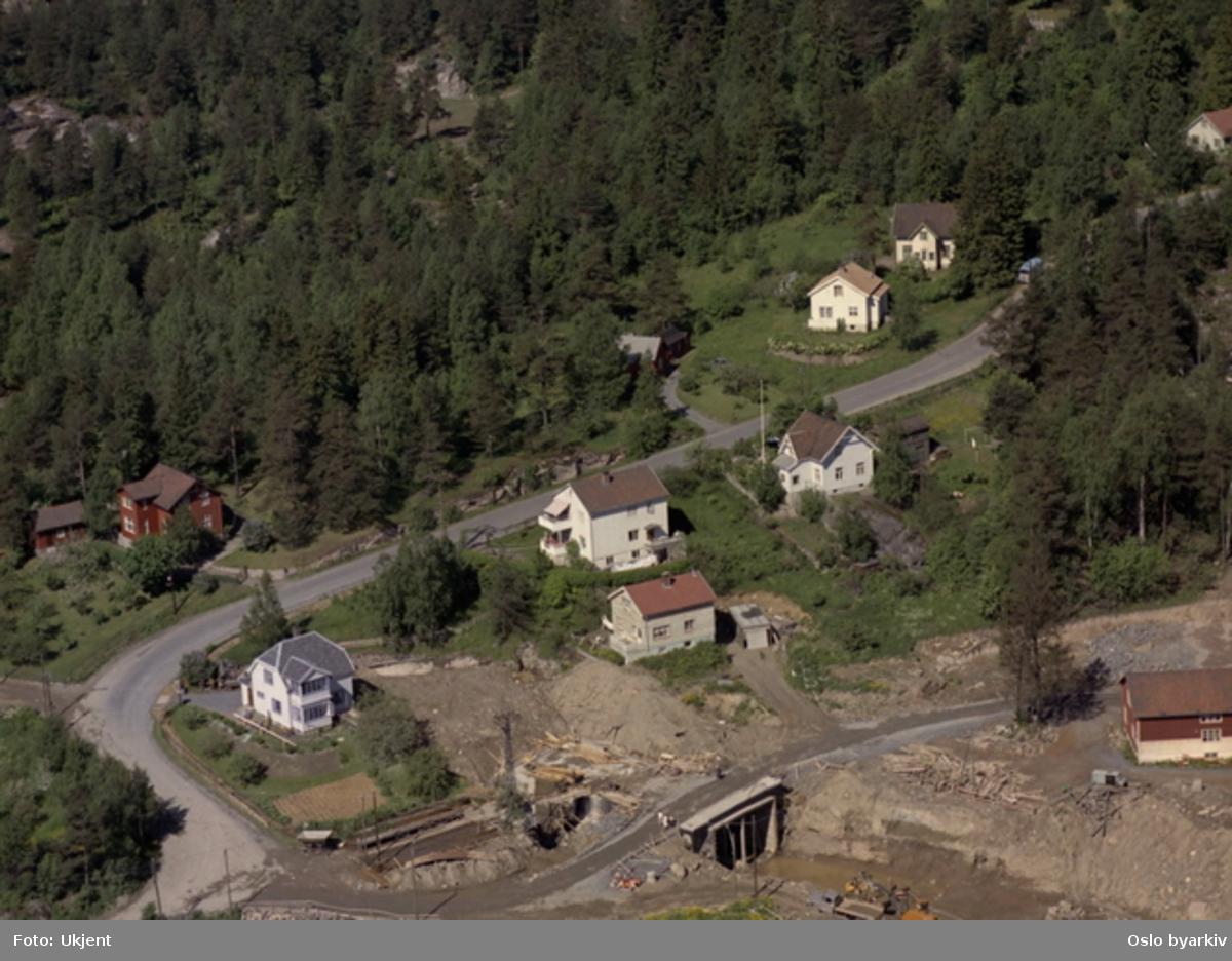 Byggingen av Ammerud t-banestasjon. Veien i bildet er Lilloseterveien. Dagens Ammerudvei går omtrent der veien krysser tunnelåpningen. (Flyfoto)