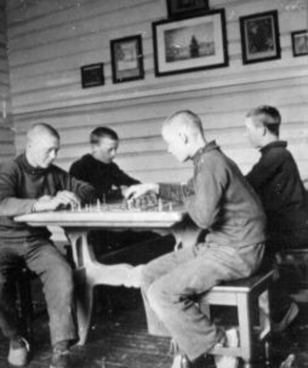 Interiør fra stue på Toftes Gave, Nedre Sund, Helgøya. 4 gutter spiller sjakk.