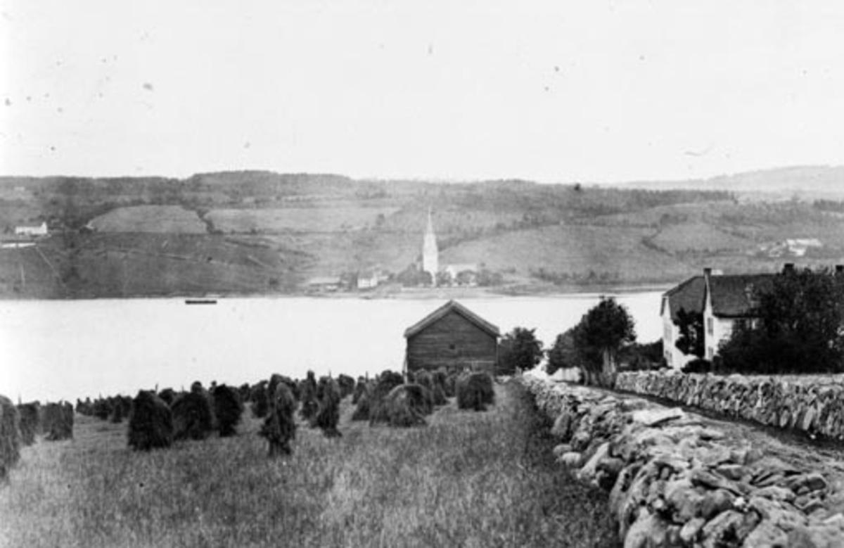 Steingjerder på Toftes Gave, Nedre Sund, Helgøya. Utsikt til Tingnes og Nes kirke. Kornband på staur (snes) til tørk.