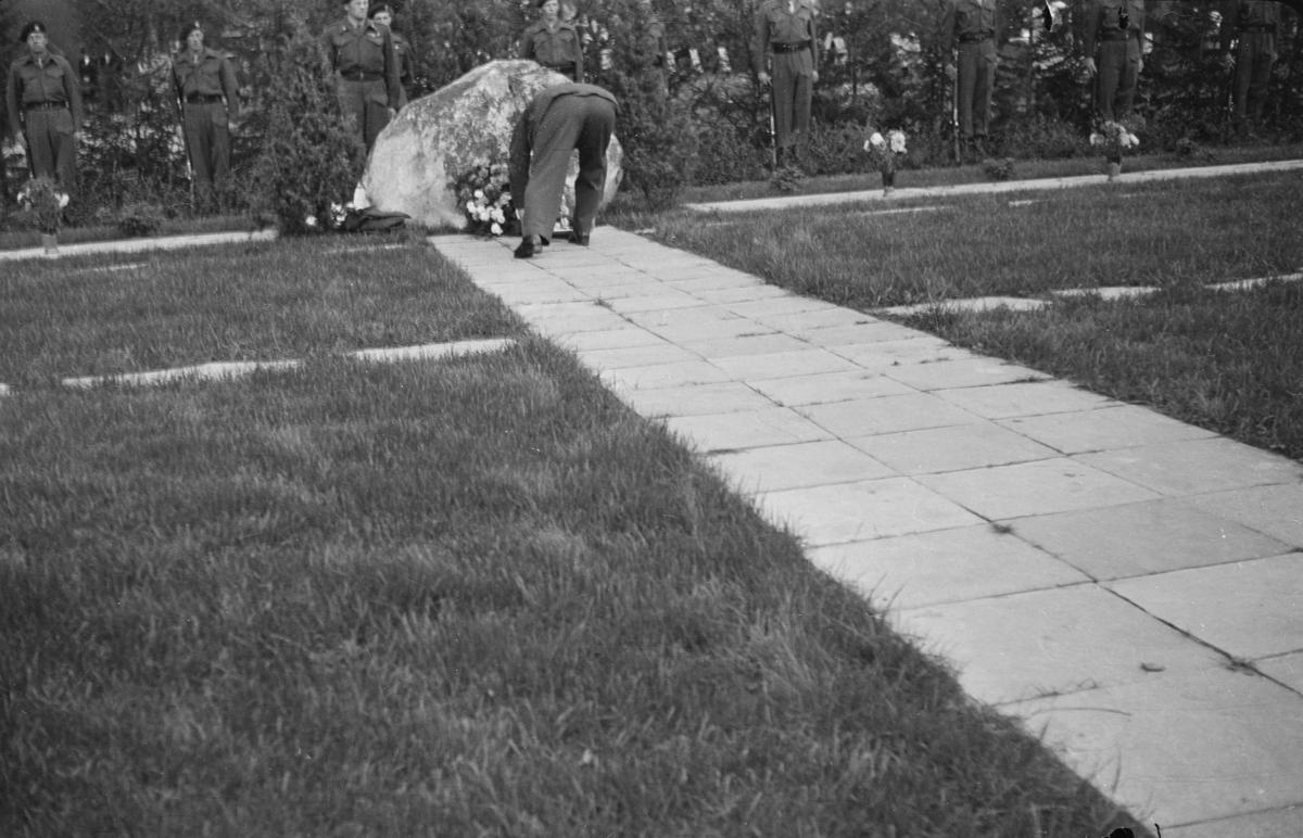 Blomsternedleggelse ved bauta på kirkegården i Elverum
