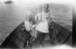 Fire jenter i en robåt.