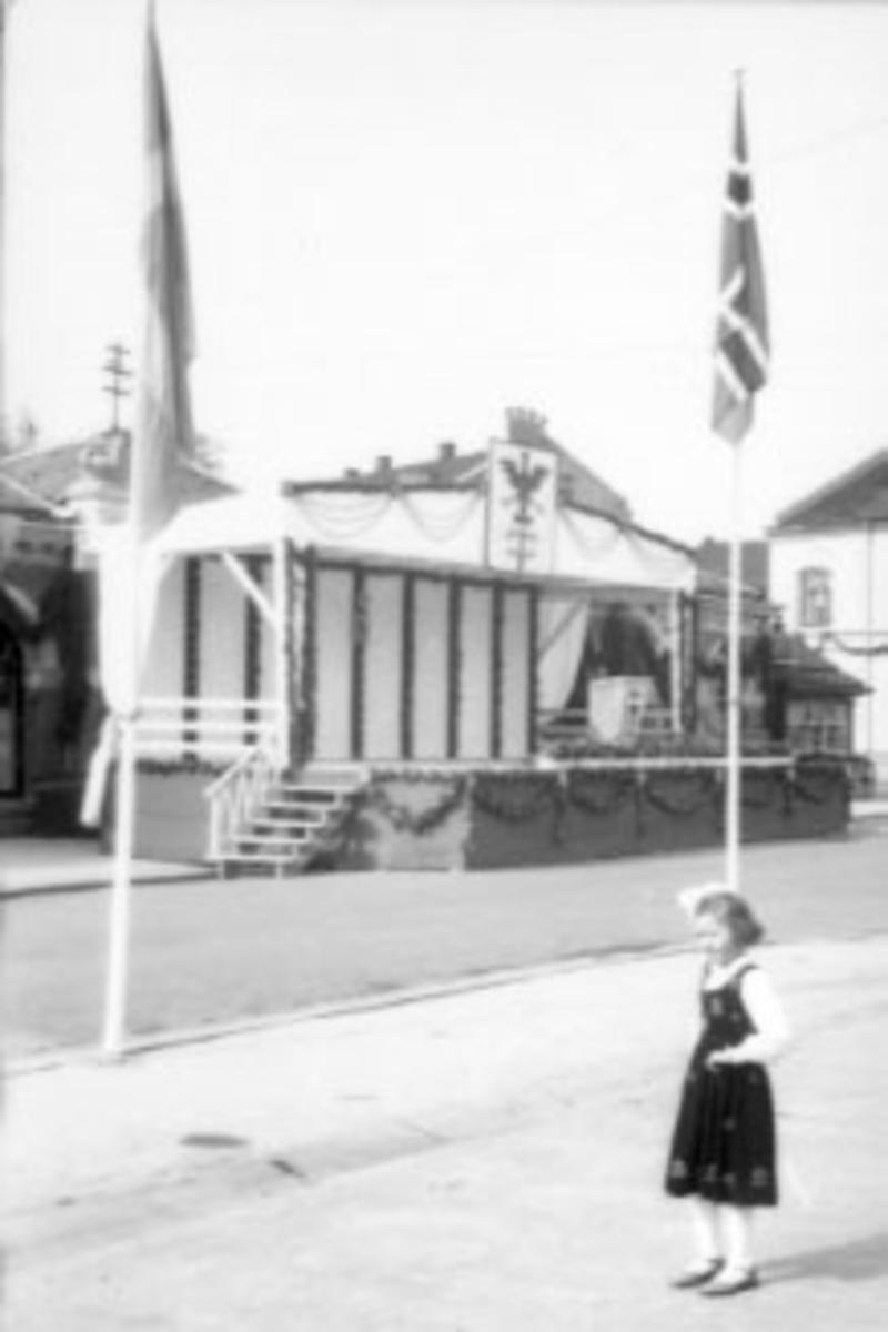 HAMAR KOMMUNE, BYJUBILEUM, 1949, FESTSCENE, ÆRESTRIBUNE, UTENFOR BASARBYGNINGEN PÅ STORTORGET. UKJENT JENTE I BUNAD