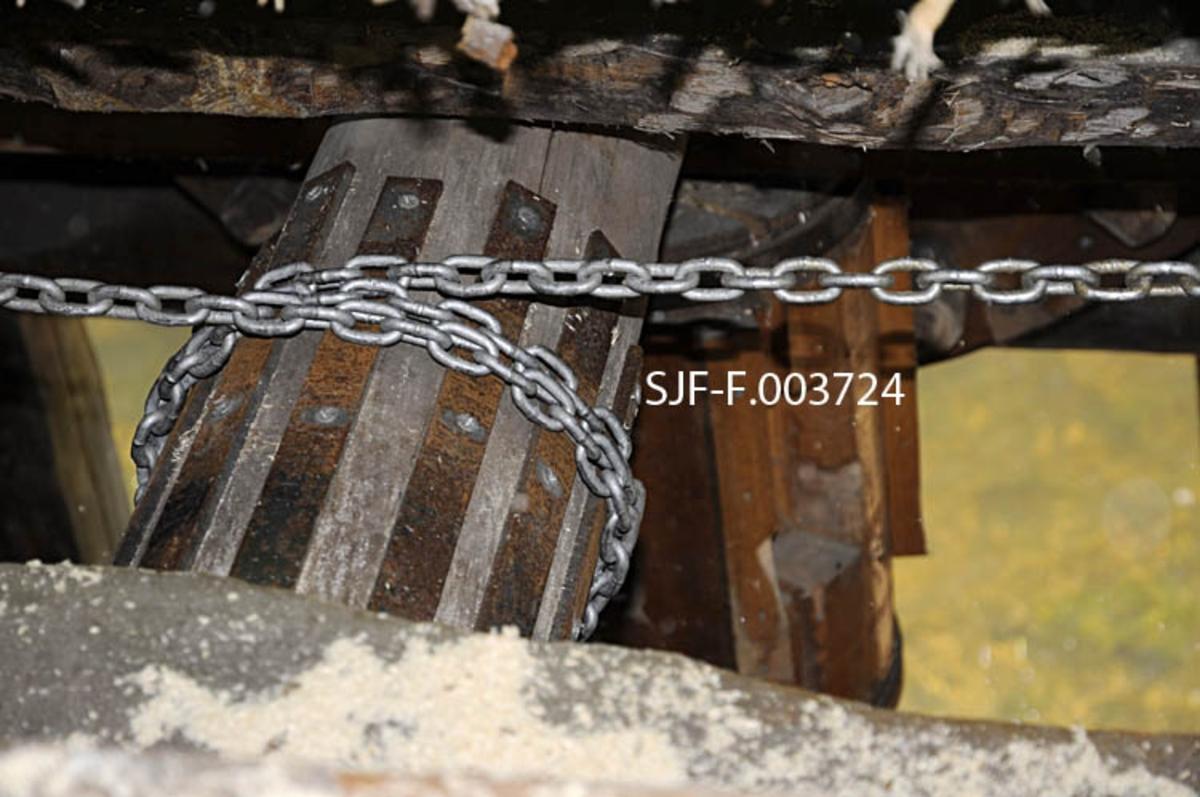 """Aksling for kjettingtrekk ved den rekonstruerte oppgangssaga ved den nederste dammen i Gjersjøelva, som danner grenselinje mellom Oslo og Oppegård kommuner.  Fotografiet er tatt gjennom ei spalte i saghusgolvet.  Bildet viser hvordan den nevnte akslingen, som brukes i framtrekket av sagbenken (også kalt """"sagvogna""""), er belslått med jernband, som skulle forebygge at kjettingen raskt ville """"gnage i stykker"""" trevirket i akslingen."""