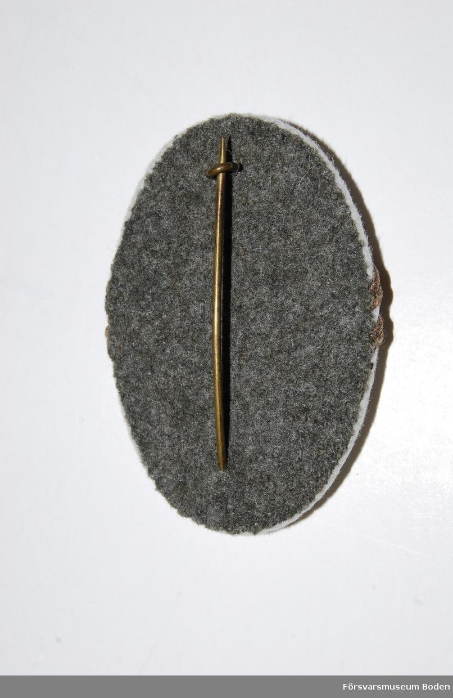 Skålformad metallbricka med vitt kläde. Nål och grått kläde på baksidan. Bronsfärgad knapp för underofficerare och upptill nationalitetsmärke m/1941. Två smala vinklade bronsfärgade galoner betecknande fanjunkare eller styckjunkare.