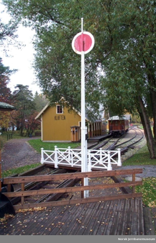 Signalskive på mast, brukt på Holstad stasjon fra 1915 til 1946. Skiven er rød med hvit kant. - For signalgivning