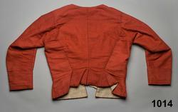 Tröja för kvinna  av rött halvylle  med mörkblå varp och rött inslag i tuskaft av redgarn,  2 fram/sidstycken med infällda skörtkilar i sidorna, 2 ryggstycken avsmalnande i  3 skörtveck som  fästs fast, isydd svängd ärm med 2 sömmar, med uppslag, påsydd bröstlapp med 6 insydda träspröt, i vardera framkanten under bröstlappen  ett insytt träspröt och 6 snörhål tränsade med blått lingarn. Bröstlappen knyts i vänster sida mot framstycket med 2 par (?) rosa sidenband. Fodrad med oblekt linnelärft. Anm.Endast ett rosa sidenband återstår som är trasigt. Rester efter motsatta bandet samt ett par till finns på bröstlappen  och nedanför på vänstersidan. Använd som brudtröja av Annika Andersdotter midsommardagen 1795. Hela bruddräkten se inv.nr 1012-1018. Även brudgummens dräkt inv.nr 1019-1021. Bilder finns i Anna-Maja Nyléns; Folkdräkter, 1971. Den svarta tröjan i kamlott liksom den svarta kjolen nr. 1012 och 1013 har sannolikt använts som ungmorsdräkt dagen efter bröllopet, medan denna röda tröja sannolikt varit för bröllopsdagen. Tyget liknar kamlott men är vävt med linvarp och med  ullgarn, men är troligen ändå ett köptyg av hög kvalitet.  J´fr. svart kamlotttröja från Arbrå i samma snitt inv.nr 1948. /Berit Eldvik okt 2005 och 2011-01-17