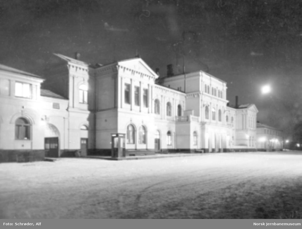 En flombelyst Trondheim stasjonsbygning fra bysiden