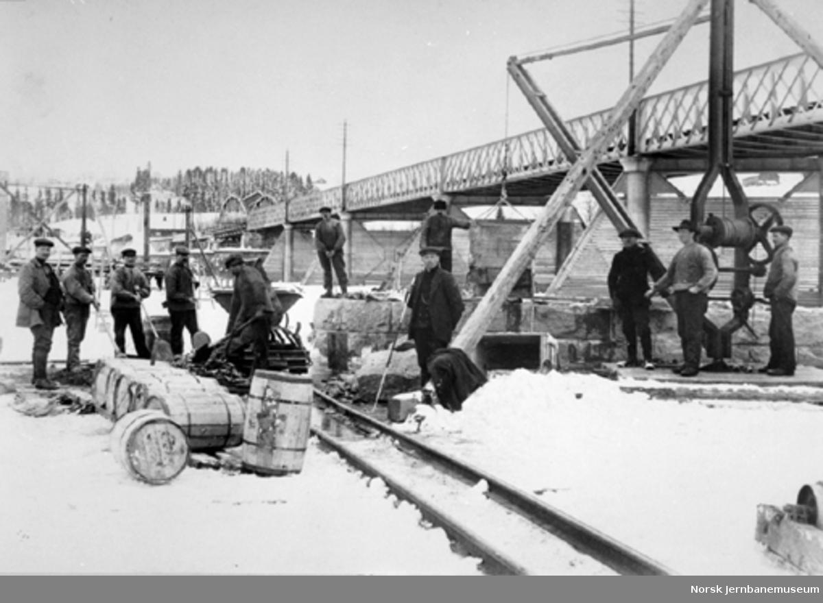 Arbeidslag på brygge (?) ved Fetsund bru ca. 1914. Vi ser bl.a. trallebane, kran og diverse tønner med sement. Til venstre oppsynsmann Ole Tohn.