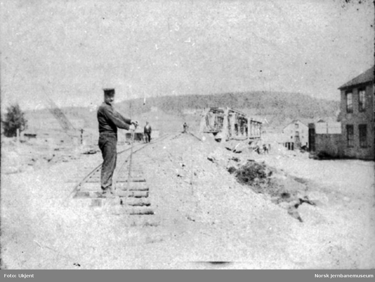 En mann står i trallesporet med en større fagverksbru i bakgrunnen på ukjent bane