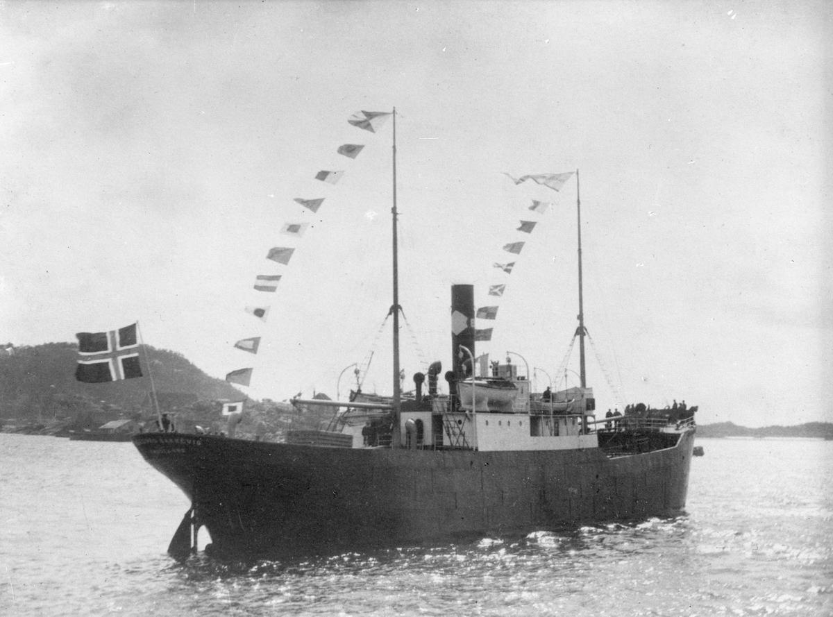 """Dampskipet D/S """"Ingeborg Bakkevig"""", med deler av mannskapet i baugen, på dekk og akter. Sjøhus og fjell i bakgrunnen."""