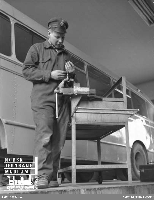 Lågendalsruten : sjåfør A. Mobæk ved arbeidsbord i verkstedet