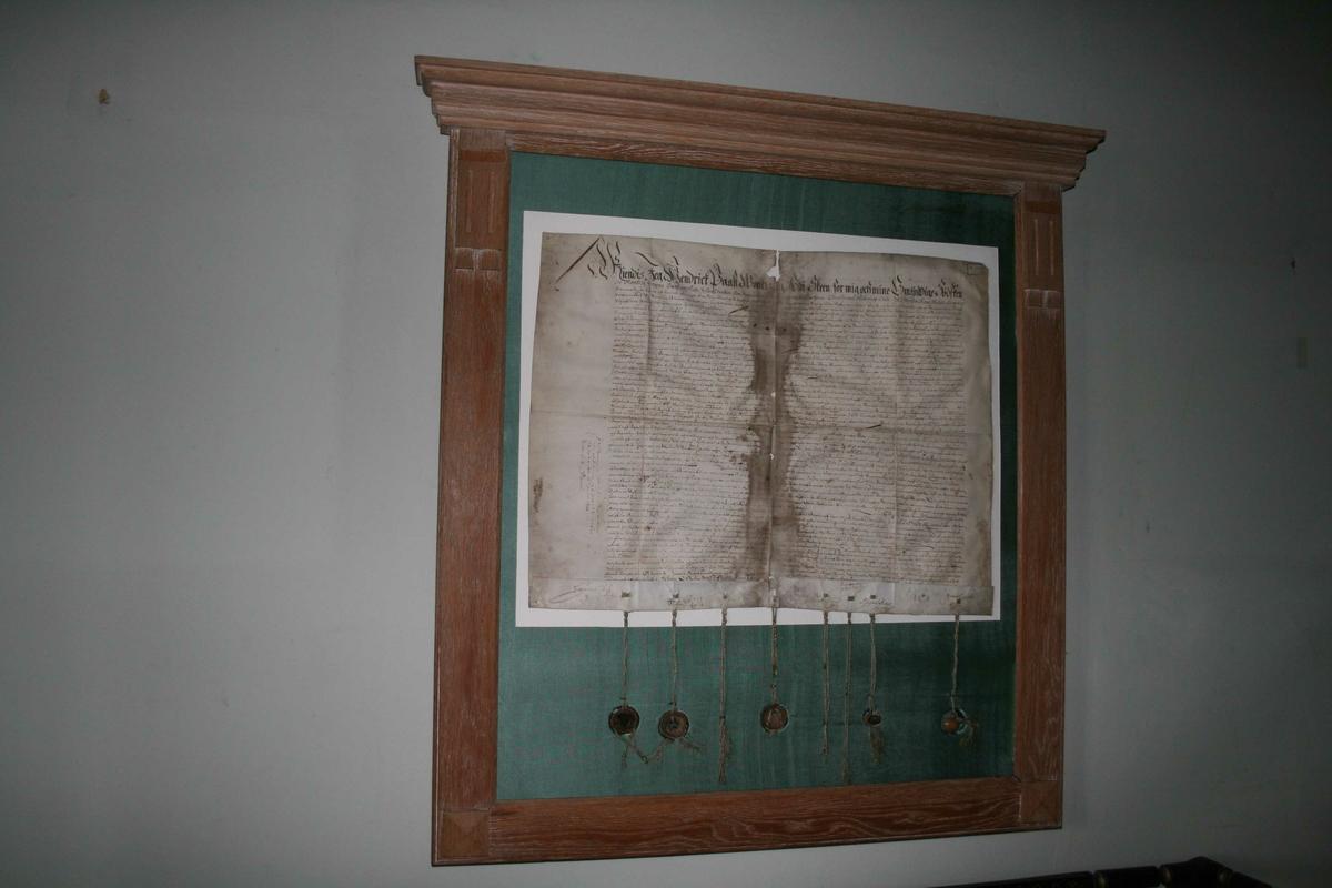 Dokument montert i glass og ramme. Nederst på dokumentet er det festet snorer med segl.