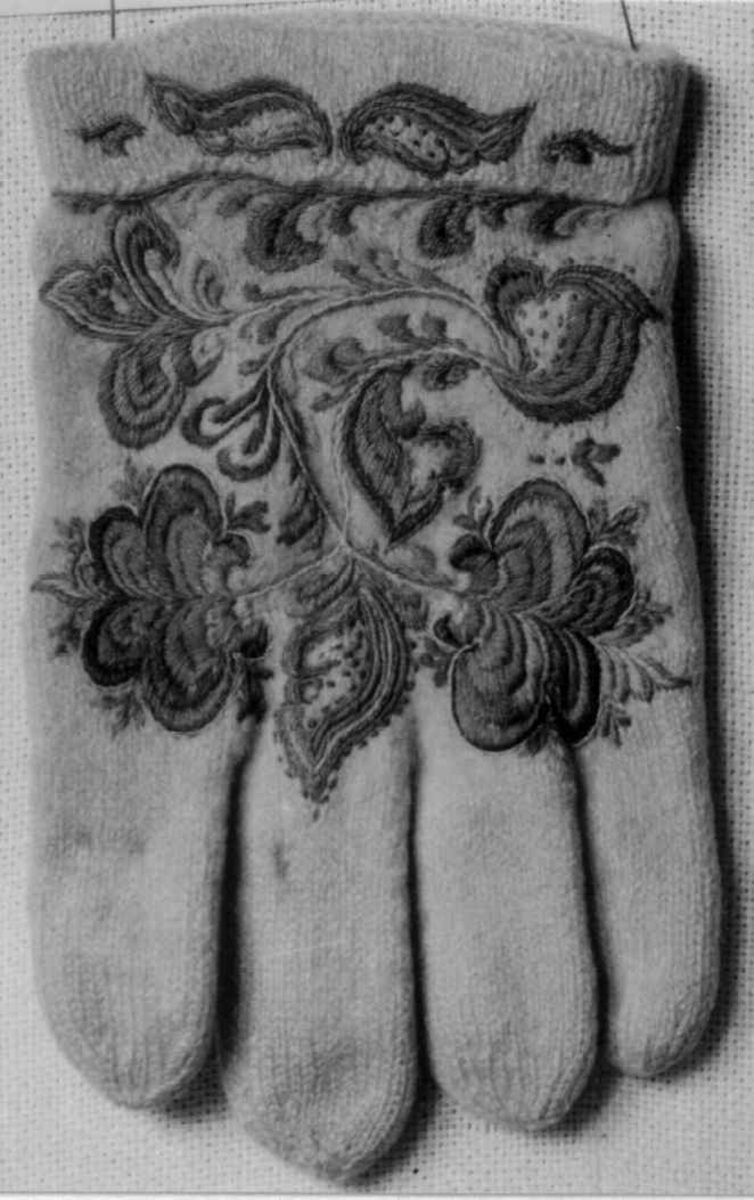 Hvite strikkede votter med flerfarget broderi.
