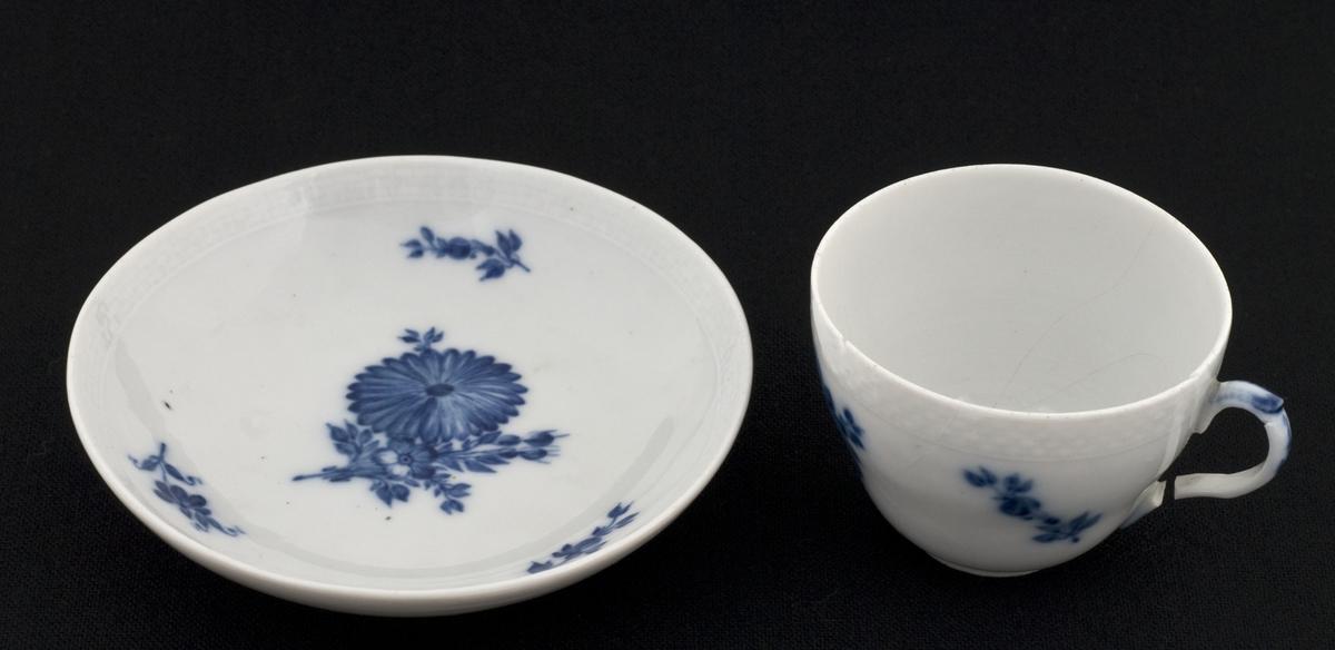 Hvit kopp og skål med blå blomst.