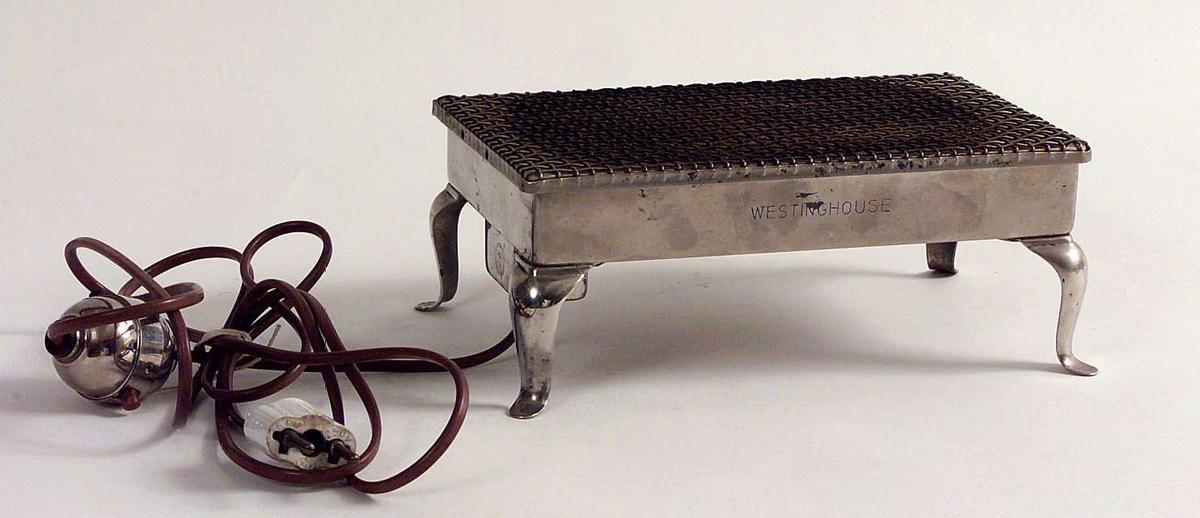 Kjelevarmer med siste patentdato 6.desember 1910. Antagelig også brukt som brødrister.