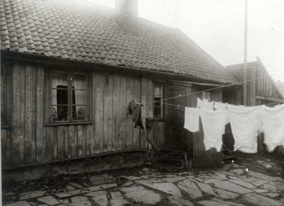 St. Halvards gate 20, Oslo. Lavt trehus, gårdsplass med klesvask.