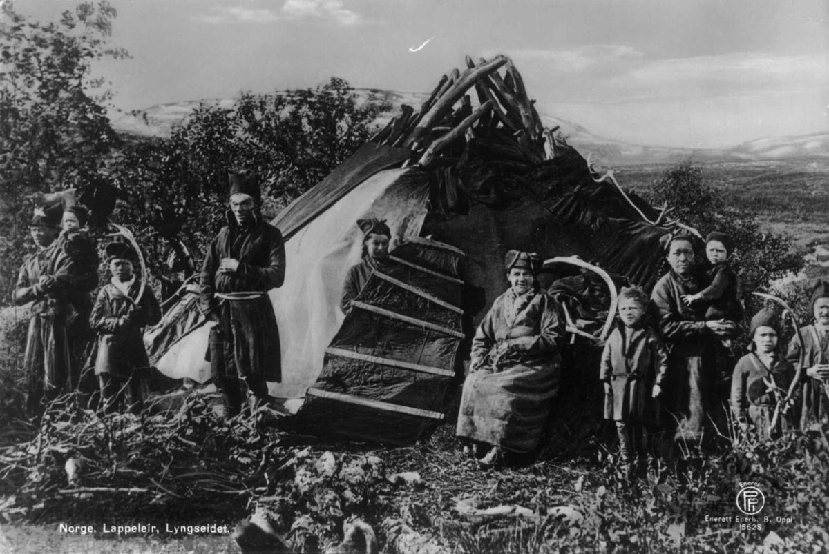 Barn og voksne samer samlet foran et telt. Middagsfjäll, Kalls Labby før 1892. Fjell og vidde i bakgrunnen.