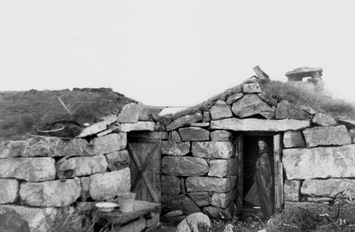 Kvinne ved bebyggelse i Bjoreiddalen på Hardangervidda.