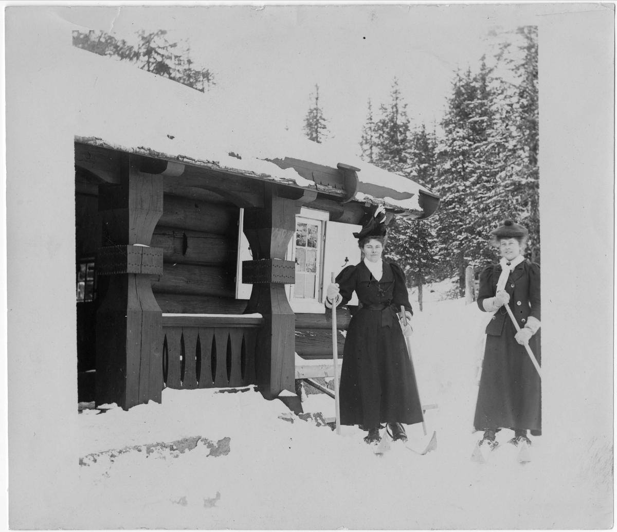 Kvinner på ski foran bygning, ukjent sted. Serie tatt av Robert Collett (1842-1913), amatørfotograf og professor i zoologi.