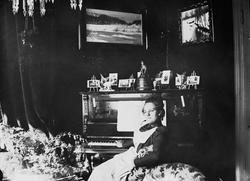 Kvinne i hvitt forkle sitter ved piano, Meltzers gate 9, Osl