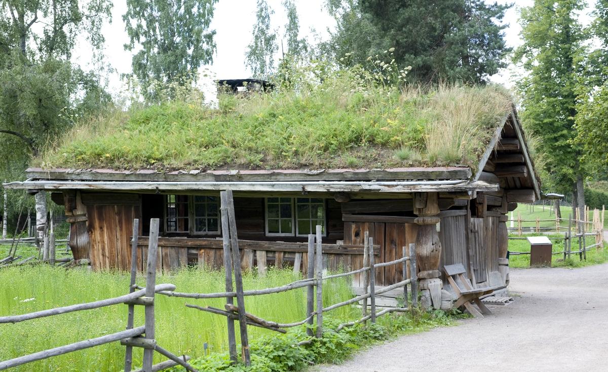 ELDHUS FRA BAKKE I ROLLAG, CA. 1750-1800  Overført til museet 1945, gjenoppført 1945  Eldhuset var gårdens «grovkjøkken» for baking, slakting og vask. Eldhuset har ett rom, og sval i fronten og på den ene langsiden. Det har forseggjort innredning: peis, vinduer og seng. Det viktigste inventaret er peisen, hvor flatbrød ble stekt på takke. I den ene sidevangen på peisen er det en luke med jerndør. Den var åpning til en bakerovn, murt opp utenfor tømmerveggen. Denne bakerovnen er ikke blitt gjenoppført på museet. Eldhuset kunne også bli brukt som sommerstue på gårder som ikke hadde egen sommerstue.   (Tekst hentet fra By og bygd 43, 2010)