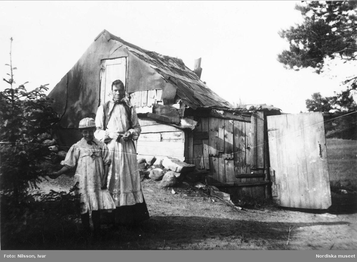 Fattigmiljö. Kvinna och hennes dotter framför fallfärdig backstuga i Enskede, Stockholm.