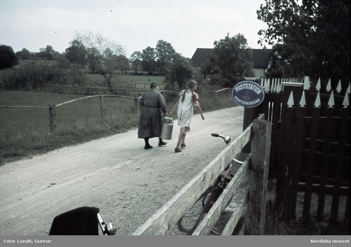 """En kvinna och en flicka går på en grusväg och hjälps åt att bära en mjölkflaska. På ett staket, en skylt med texten """"Poststation/Postsparbank""""."""
