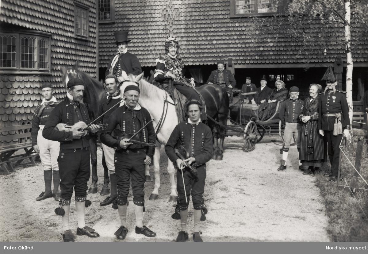 """Bröllop. """"Skansen, Delsbobröllopet, Sept 1929"""".  Framför brudparet (som enligt tradition sitter till häst) står spelmännen Finn-Jonke, Thore och Sven Härdelin. I en grupp t h står tre kända hälsingar; Bror Hillgren, Delsbostintan och Fredrik Winblad von Walter."""