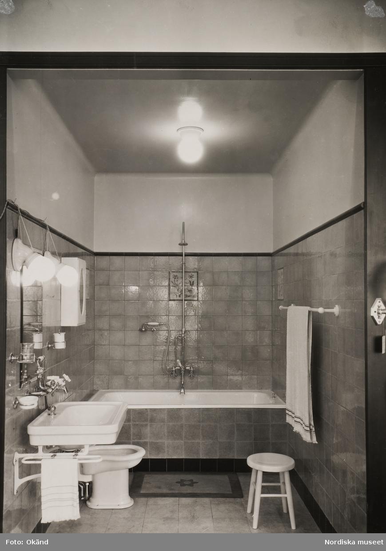 Interiör från ett halvkaklat badrum. badkar, handfat, bidé ...