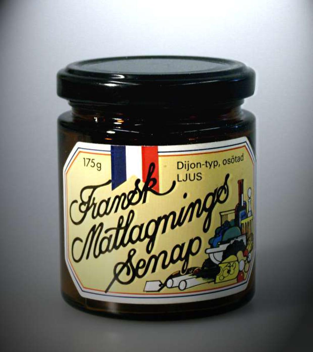 Brun glasburk för senap med svart plåtlock. Gul pappersetikett med text i svart: Fransk Matlagnings Senap.